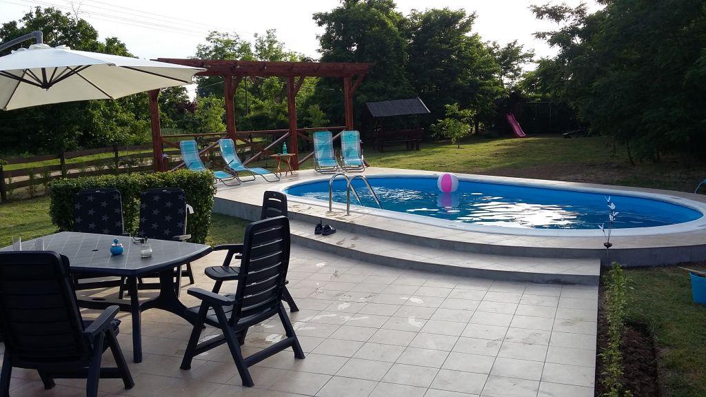 diepe tuin met zwembad en diverse zitjes